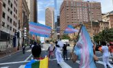 protestors holding trans flags march down a street
